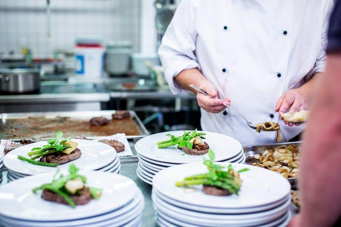 A chef preparing plates of food in a restaurant