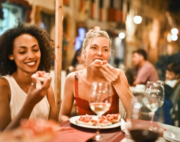 Two women enjoying delicious food at a restaurant