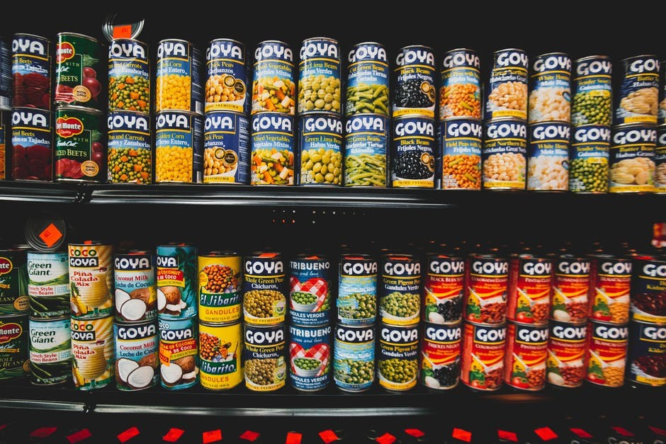 Food cans displayed on a grocery store shelf